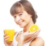 Woman holding orange and orange juice — Stock Photo