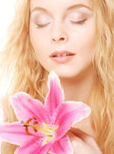Woman with pink lily high-key portrait — Stock Photo