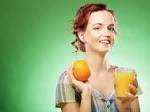 橙汁在绿色背景的女人 — 图库照片