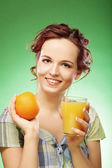 Woman with orange juice over green background — Stock Photo