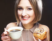 Woman eating cookie and drinking coffee. — Stock Photo