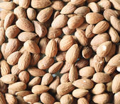 Heap of raw almonds nuts background — Stock Photo