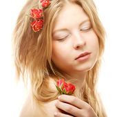 Beautiful woman with roses in hair — Stock Photo
