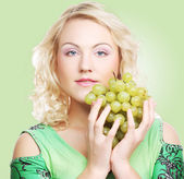 Young blond woman with grape — Stockfoto