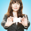Friendly woman holding a business card and smiling — Stock Photo #27636751
