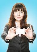 Sympathique femme tenant une carte de visite et souriant — Photo