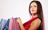 Cute young woman shopping with color bags — Stock Photo