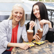 Smiling women drinking a coffee sitting — Stock Photo
