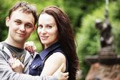 Kärleksfull unga paret sitter av en fontän — Stockfoto