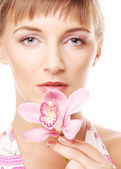 Young beautiful woman with pink flower — Stock Photo