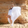 Stock Photo: Womin white dress dancing on desert