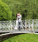 Couple walking on a bridge in park — Stock Photo
