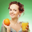 Woman with orange juice over green background — Foto Stock
