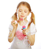 Funny lovely little girl blowing soap bubbles — Stock Photo