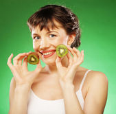 Young smiling woman holding kiwi. — Stock Photo