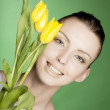 Woman with yellow tulips over green background — Stock Photo