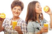 Two women with orange juice. — Stock Photo