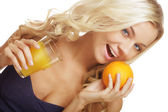 Woman holding orange and juice — Stock Photo