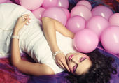 Sleeping woman lying on floor among balloons — Stock Photo