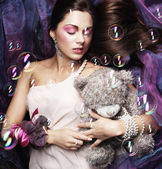 Woman lay on organza with teddy bear — Stock Photo