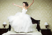 Happy bride jump on bed. — Stock Photo