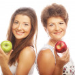 Middle age woman with her daughter holding apples — Stockfoto
