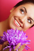 Beautiful woman with big purple flower — Stock Photo