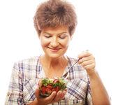 Mature smiling woman eating salad — Stock Photo