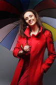 Woman in red coat with umbrella — Stock Photo