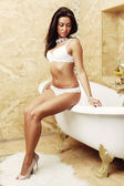Sexy lingerie woman posing near a bath — Stock Photo