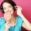 Beautiful woman with headphones and candy — Stock Photo