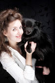 Woman holding black dog — Stock Photo