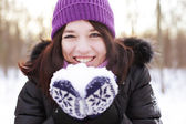 Woman in winter park, blowing snow playfully — Stock Photo