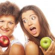 Middle age woman with her daughter holding apples — Stock Photo