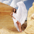 Woman in white dress dancing on the desert — Stock Photo