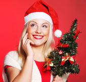 Woman with Santa hat holding christmass tree — Stok fotoğraf