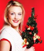 Woman holding Christmas tree — Stock Photo
