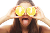 Funny girl holding oranges over eyes — Stock Photo