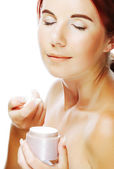 Young smiling woman applying cream on her face — Stock Photo