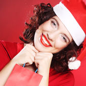 Woman with Santa hat holding shopping bag, — Stock Photo