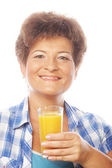 Mature woman holding a glass of orange juice — Stock Photo