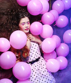 Sleeping woman lying on floor among balloons — Stock Photo