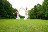 Två unga flickor hoppa i sommaren park. — Stockfoto