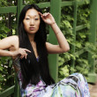 Asian woman sitting on the park bench — Stock Photo