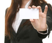 Friendly woman holding a business card and smiling — Stock Photo