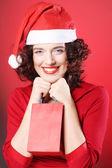 Vrouw met Kerstmuts houden boodschappentas, — Stockfoto