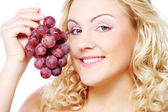 Young blond woman with grape — Foto Stock
