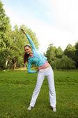 Sportieve vrouw springen op groen gras — Stockfoto
