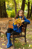 Young woman with autumn leaves sitting on bench — Stock Photo