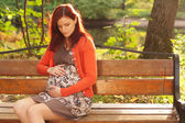 Beautiful pregnant woman walking in autumn park — Stok fotoğraf
